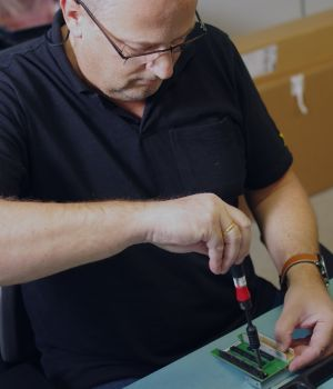 A man in a polo shirt tightening a screw on a electrical component