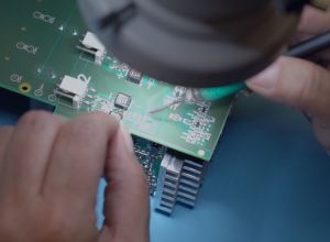 Two hands soldering on a circuit board