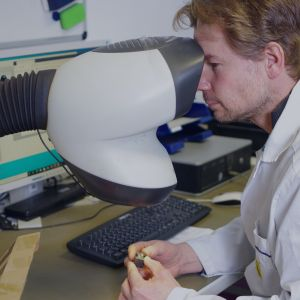 A man in a lab coat looking into a microscope